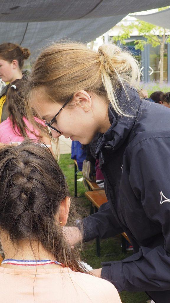 Die Grundschüler/innen freuen sich über die Hilfe der P-Seminar-Teilnehmerinnen beim Basteln.